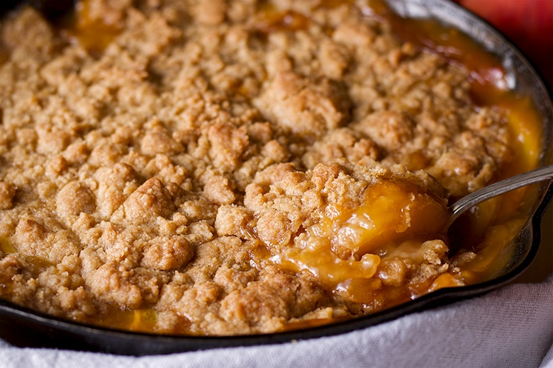 Scooping out a spoonful of peach cobbler from a cast iron pan.