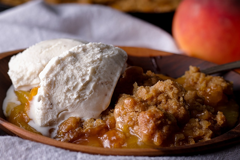 A bowl of warm peach cobbler with vanilla ice cream.