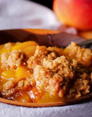 A bowl of peach cobbler with brown sugar cookie topping.