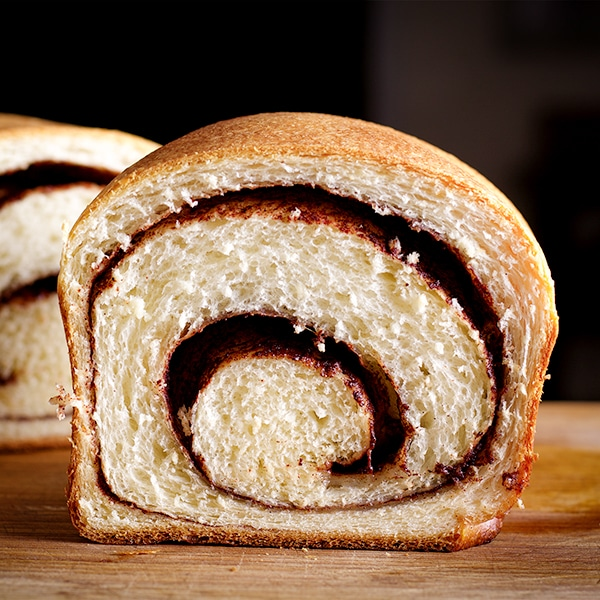 A loaf of homemade cinnamon bread, cut in half so you can see the cinnamon swirl inside.