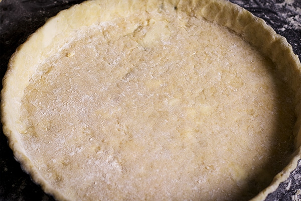 A tart pan lined with pastry dough, ready to be baked.