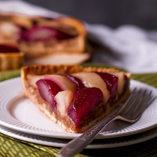 A slice of Pear Tart with Frangipane and Wine Poached Pears