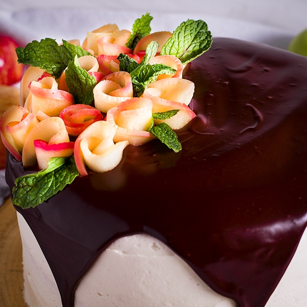 Apple roses decorate the top of an apple layer cake iced with cider buttercream and topped with Chocolate Ganache.