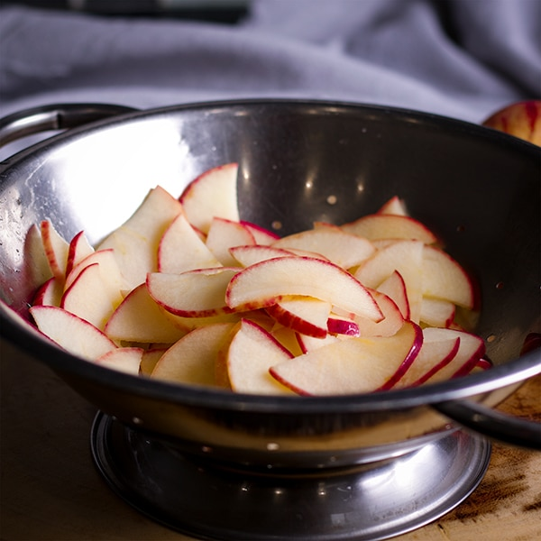 A colander of apple slices that have just been blanched in sugar water for making apple roses.