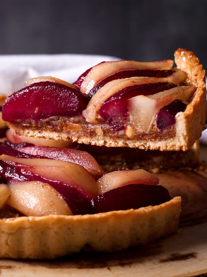 Serving a slice of Pear Tart with Frangipane and Wine Poached Pears