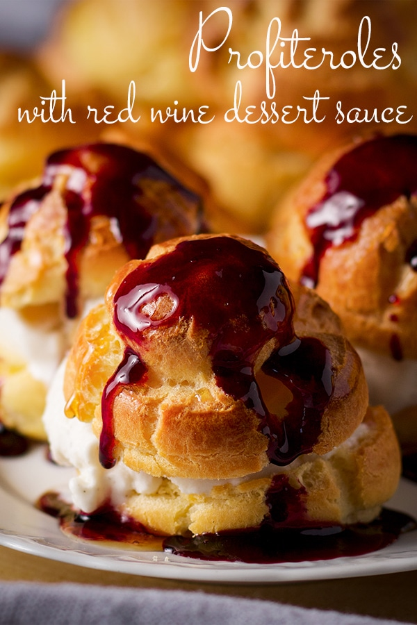 A plate of homemade profiteroles filled with vanilla ice cream and drizzled with sweet wine dessert sauce.