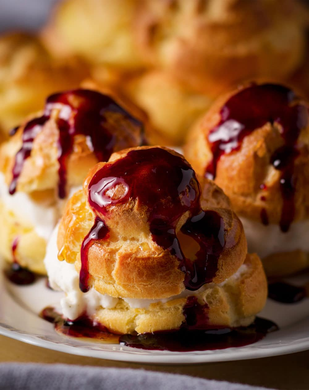 A plate of three profiteroles filled with vanilla ice cream and drizzled with red and white wine reduction dessert sauce.
