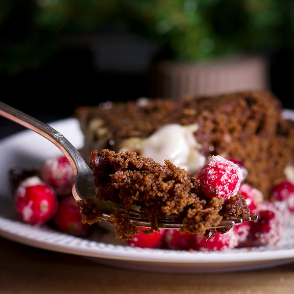 Taking a bite of gingerbread cake with lemon glaze and sugared cranberries.