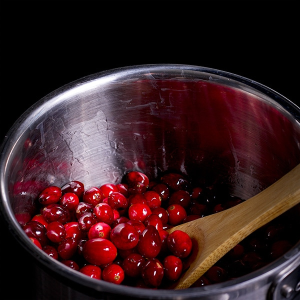 Tossing cranberries in sugar syrup to make sugared cranberries.