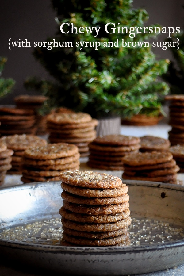 Mini Gingerstap cookies stacked on a plate with more cookies and Christmas trees in the background