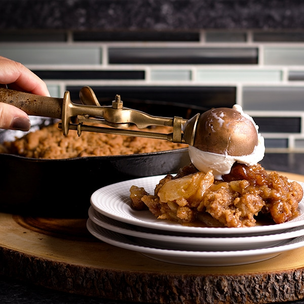 Topping a serving of Apple Cobbler with a scoop of Vanilla Ice Cream.