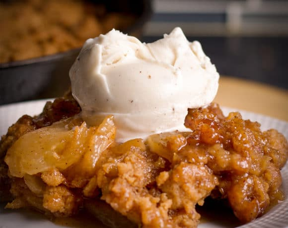 A serving of Apple Cobbler topped with a scoop of vanilla ice cream.