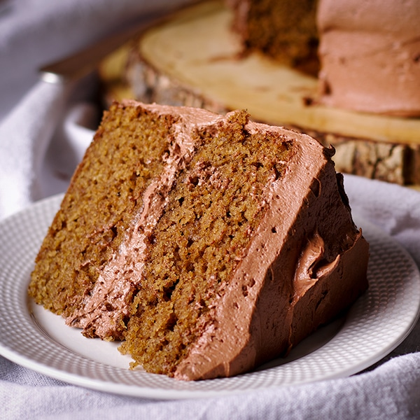 A slice of spice cake frosted with Chocolate Buttercream.
