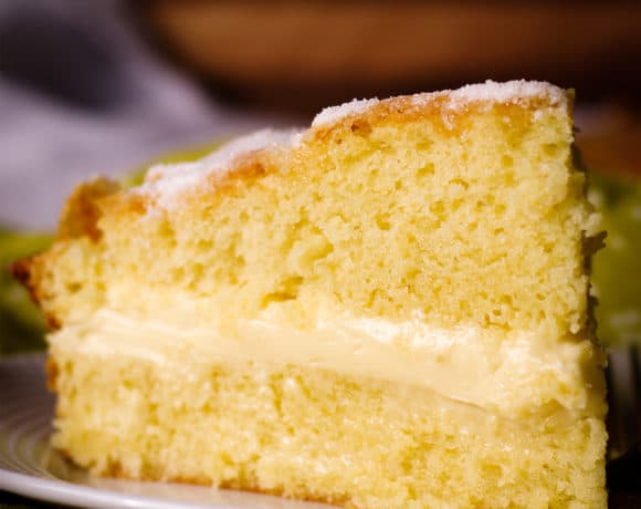 A slice of olive oil cake filled with lemon mascarpone pastry cream on a plate, ready to eat.