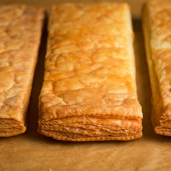 Three golden brown layers of puff pastry ready to be used for a Napoleon with Cannoli Filling.