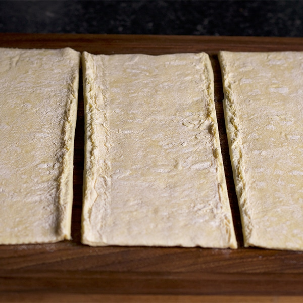 Cutting a sheet of puff pastry into thirds before baking it into Napoleon layers.
