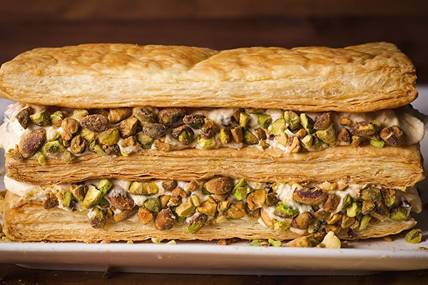 A Napoleon with Cannoli filling and pistachios on a plate, ready to serve.