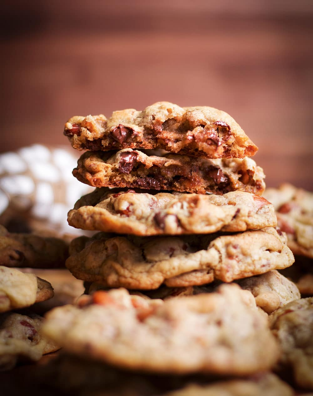 A stack of Anything Cookies with one cookie on the top broken in half to see inside.