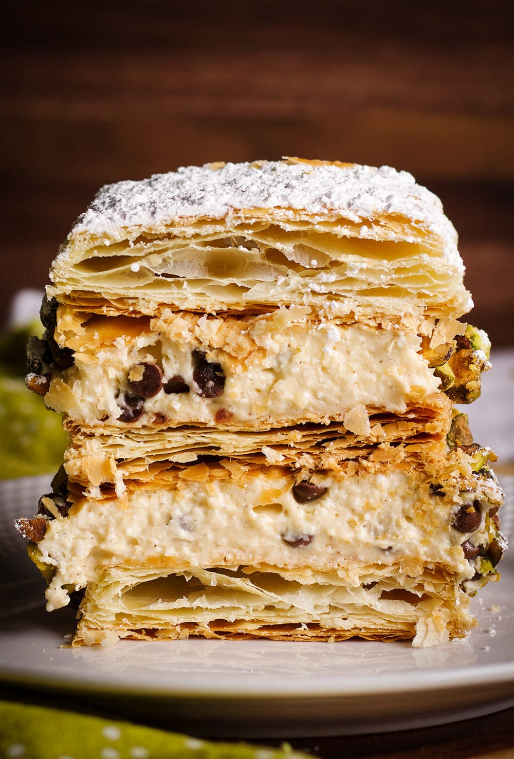 A slice of Cannoli Napoleon on a plate, ready to eat.