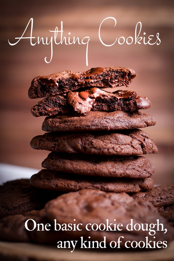Several chocolate cookies stacked on top of each other with the top cookie broken in half so you can see the gooey, chocolatey middle.