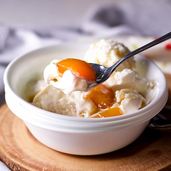 Lifting a spoonful of ice cream topped with roasted peaches and brown butter maple sauce.