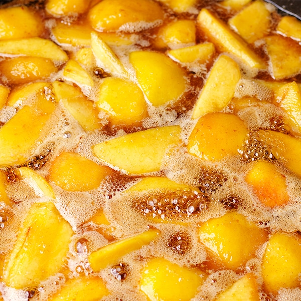 Cooking roasted fruit in a maple brown butter sauce.