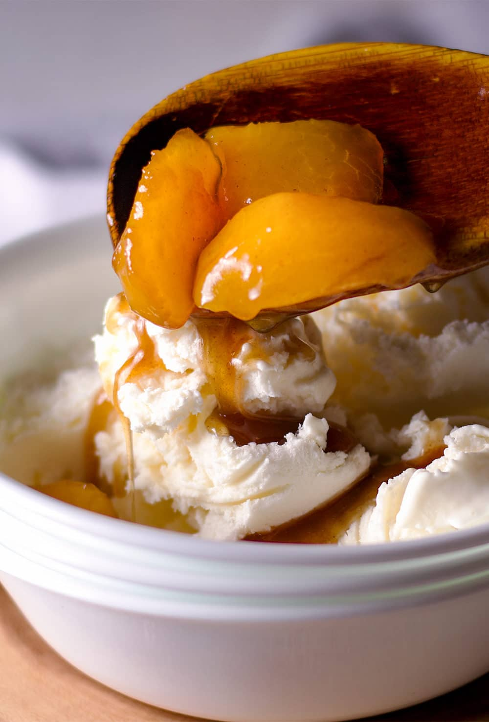 Spooning roasted fruit in brown butter maple sauce over vanilla ice cream.