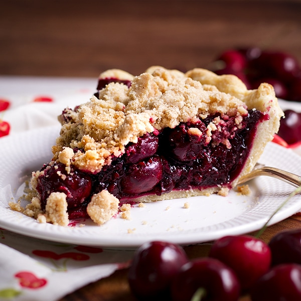 A slice of Cherry Crumb Pie on a plate, ready to eat.