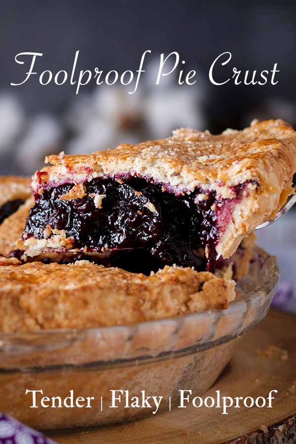 Someone using a pie server to lift a slice of double crust blueberry pie from the whole pie.