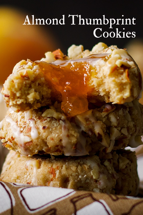 A stack of three Almond Thumbprint Cookies with a bite taken out of the top cookie and peach preserves spilling out of it.