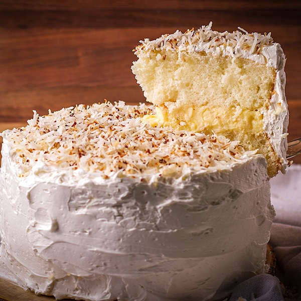 Serving a slice of coconut cream cake frosted with coconut buttercream.