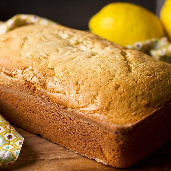 A freshly baked lemon loaf cake, cooling on a wooden board.