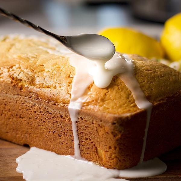 Pouring lemon glaze over a freshly baked lemon loaf cake.