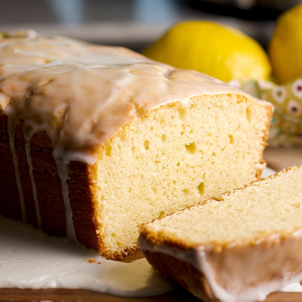 A sliced lemon loaf cake with tart lemon glaze.