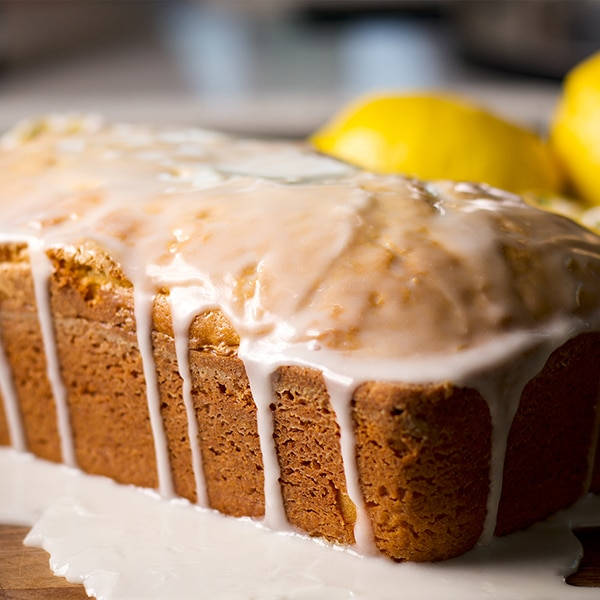 A lemon loaf cake on a wooden tray, covered in lemon glaze.