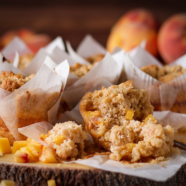 A tray of peach cobbler muffins with one muffin broken into so you can see the inside.