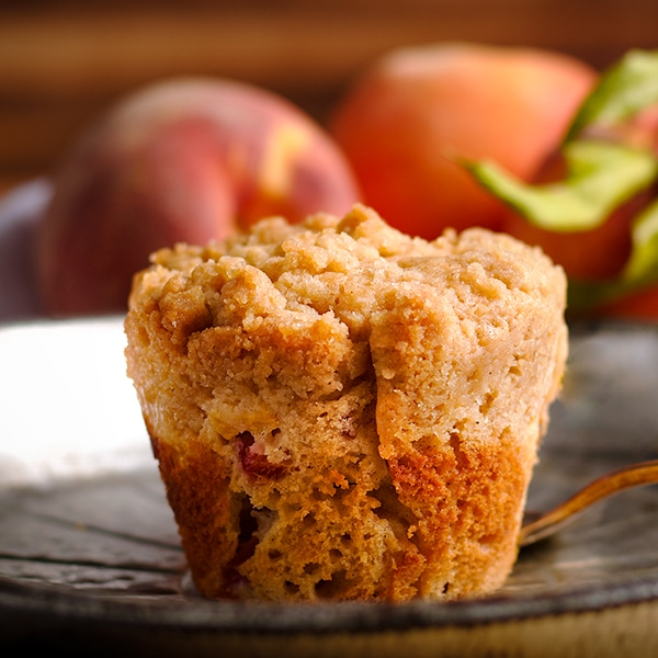 A peach cobbler muffin on a plate, ready to be topped with peach sauce.