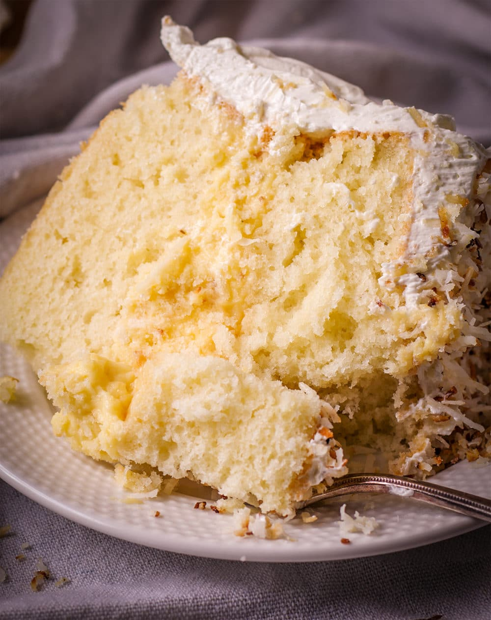 A slice of coconut cream cake on a plate, ready to eat.