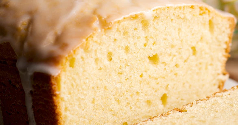 A sliced lemon loaf cake with tart lemon glaze.