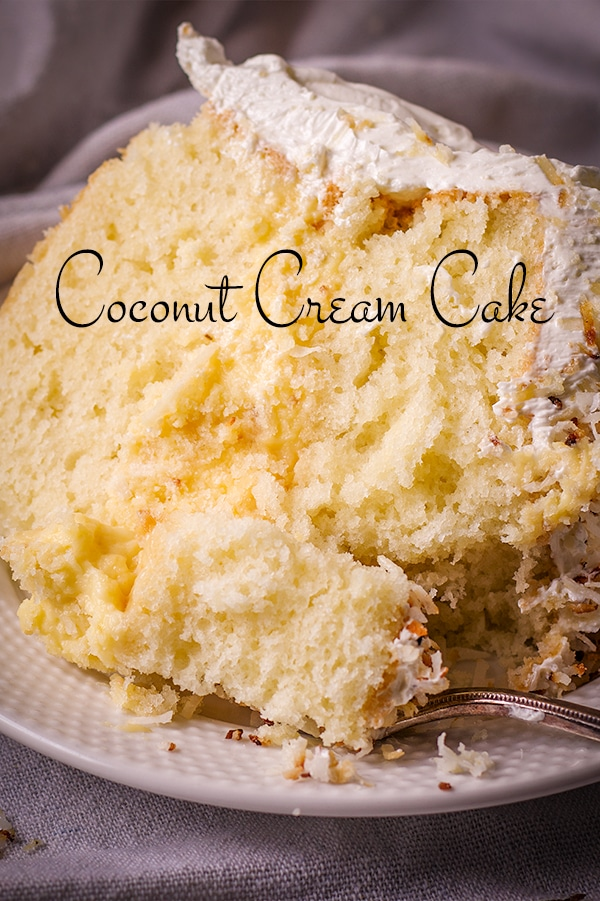 A slice of coconut cream cake on a plate with a fork, ready to eat.
