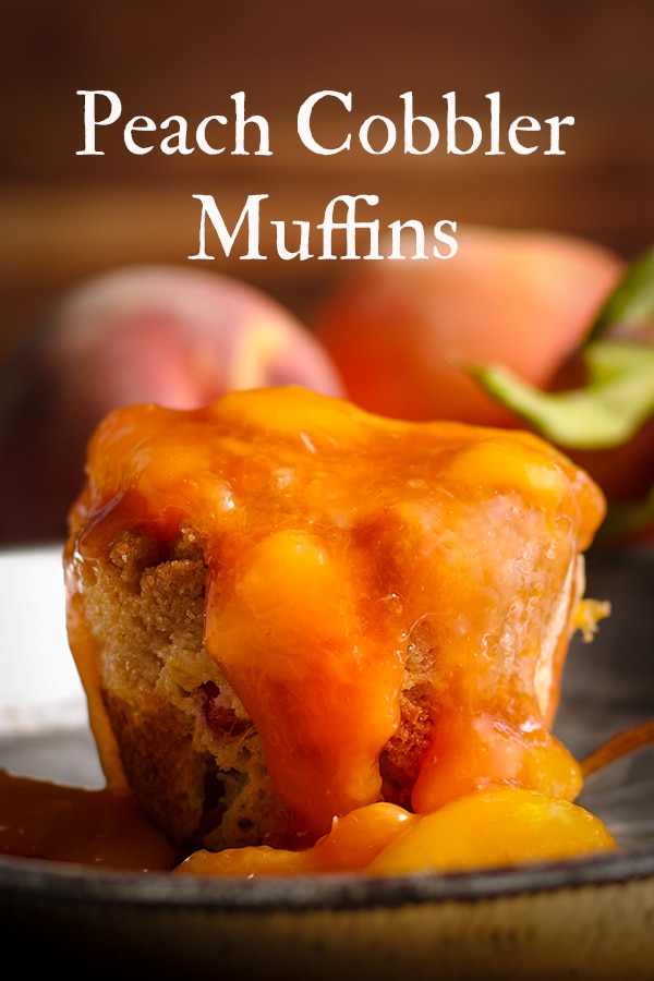 A peach cobbler muffin on a plate, covered in peach sauce, ready to eat.