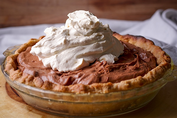 Topping a chocolate cream pie with toasted almond crust with whipped cream.