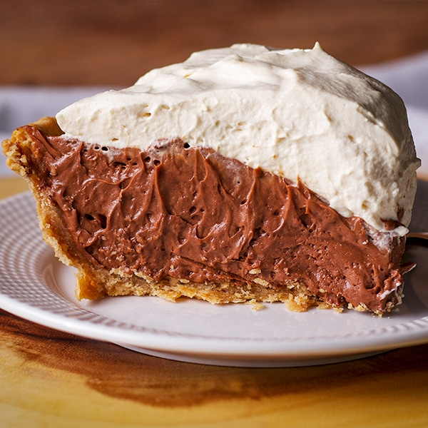 A slice of extra rich and creamy chocolate cream pie with toasted almond crust.