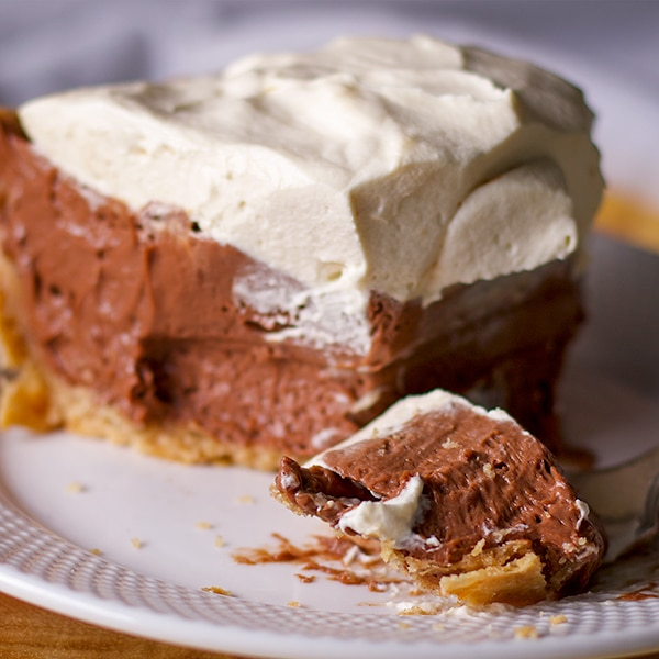 Taking a bite of rich chocolate cream pie with toasted almond crust.