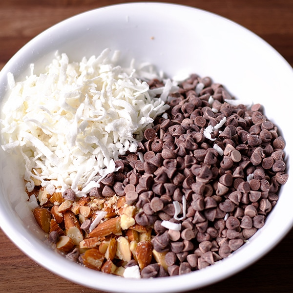 A bowl of chopped almonds, chocolate chips, and shredded coconut.