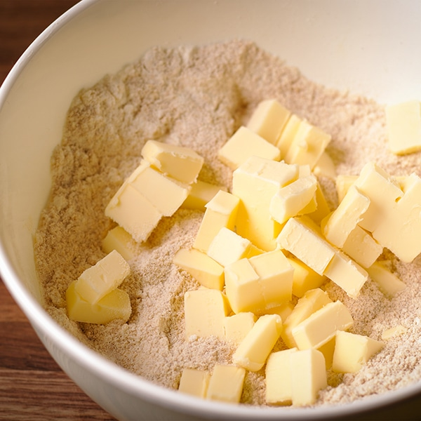 Adding butter to the dry ingredients to make toasted almond pie crust.
