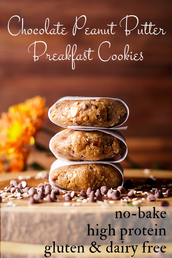 Three parchment wrapped no-bake, high protein breakfast cookies stacked on top of each other on a wooden tray.