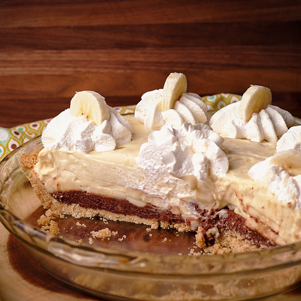 A Black Bottom Banana Cream Pie decorated with whipped cream and slices of banana.