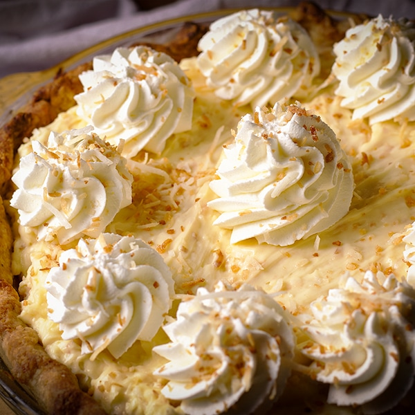 A coconut cream pie decorated with whipped cream and toasted coconut.