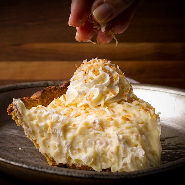 Sprinkling toasted coconut over a slice of coconut cream pie.